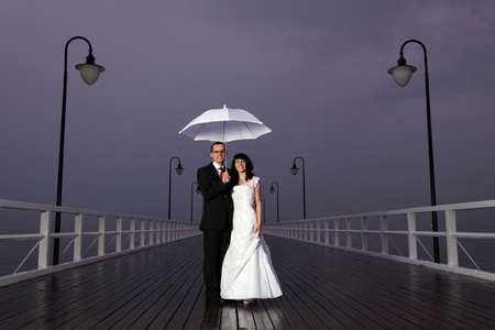 bride and groom, pier cloudy dusk sky. photo