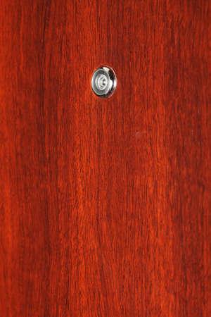 peephole: Peephole on wooden door