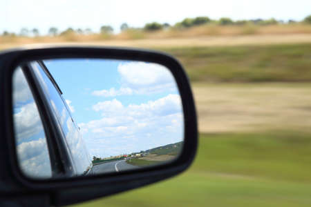 see side: Road reflecting in the sideview mirror of a car