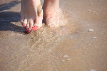nice legs in water, nice pedicure red nail sand beach Stock Photo - 10659199