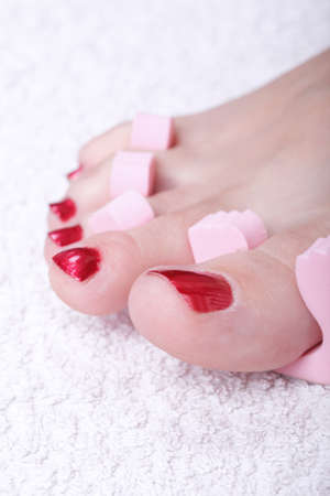 Close-up of female feet with red polished nails carefree, chiropody Stock Photo - 10689230