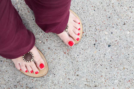 feet of a caucasian woman wearing red nail-polish and flip-flops photo