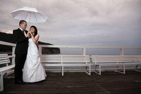 novia y el novio, el cielo muelle atardecer nublado.