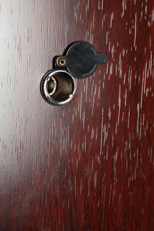 Peephole on wooden door - judas hole spyhole photo