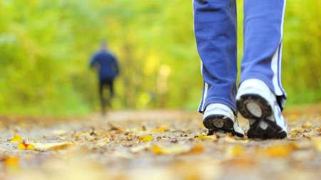 Mujer caminando a campo traviesa y pista en el otoño de los bosques Foto de archivo