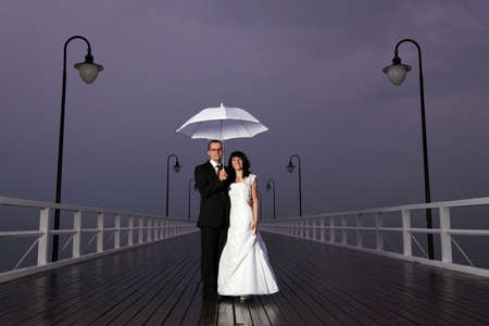 mol: bride and groom, pier cloudy dusk sky.