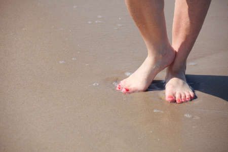 nice legs in water, nice pedicure red nail sand beach Stock Photo