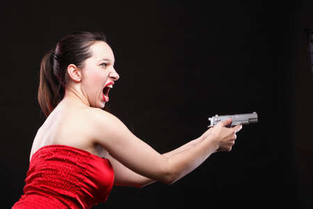Sexy young woman in red with a gun on black background Stock Photo - 11344591