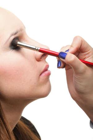 Woman applying eyeshadow using professional makeup brush isolated on white photo