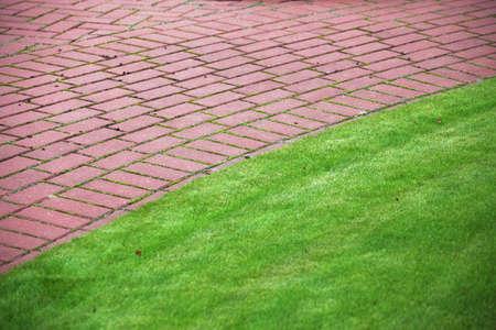 Garden stone path with grass growing up between and around stones, Brick Sidewalk photo