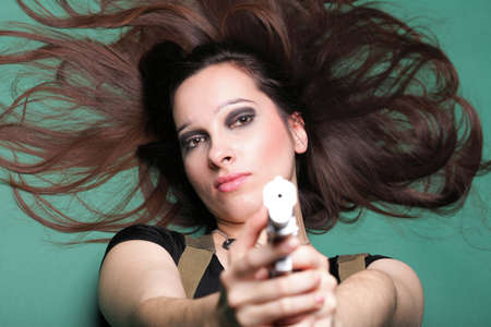 Sexy young woman in red with a gun, on green background Stock Photo - 11567669