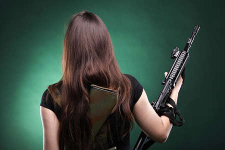 Beautiful woman with rifle plastic Military Army girl Holding Gun green background Stock Photo - 11567609