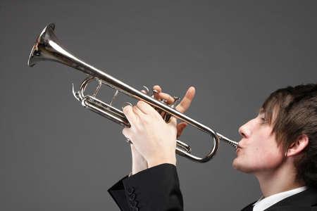 Retrato de un hombre joven de jazz tocando su trompeta fondo gris