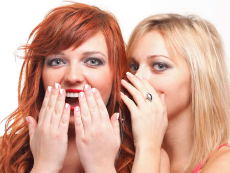 blab: two happy young girlfriends blond and ginger talking white background - society gossip, rumor, rumour