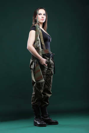 Beautiful woman with rifle plastic Military Army girl Holding Gun green background Stock Photo - 11706324