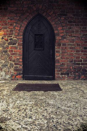 teutonic: Polonia vecchio castello Nidzica Teutonico vecchio. Vecchia porta di legno sul muro di mattoni Grunge