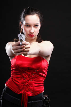 Sexy young woman in red with a gun on black background photo