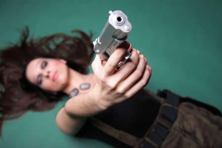 Sexy young woman in red with a gun, on green background Stock Photo - 11706361