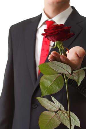 Giovane che presenta un fiore - rosa rossa isolato sfondo bianco