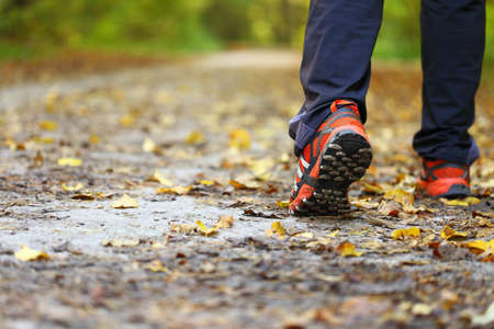 the sole of the shoe: man walking cross country and trail in autumn forest Stock Photo