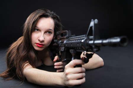 Les femmes sexy - jeune fille tenant un fusil d'assaut, fond noir