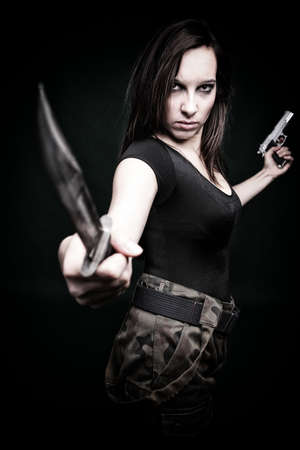 Sexy young woman in red with a gun, knife on green background Stock Photo - 11798802