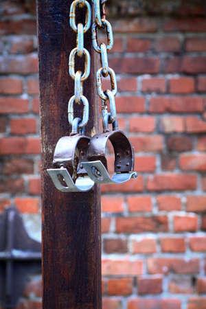 manacles: cadenas de edad, esposas de ladrillo de dos anillos antiguos de hierro oxidado en la pared de fondo