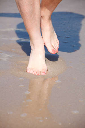 buenas piernas en el agua, bonita playa de arena roja pedicura uñas