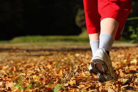 Mulher que anda de cross country e trilha na floresta do outono