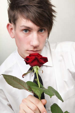 Portrait of a young man grey background. Love and rose. Stock Photo - 12149746