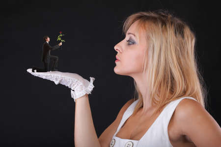 Man giving beautiful blonde woman a rose - white gloves black background photo