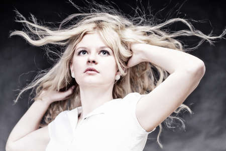 Blonde woman with her hair blowing in the wind photo