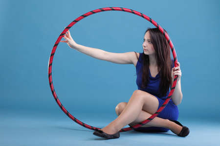Beautiful woman in a sport wear. Dance hoop gym exercises blue background Stock Photo - 11964812