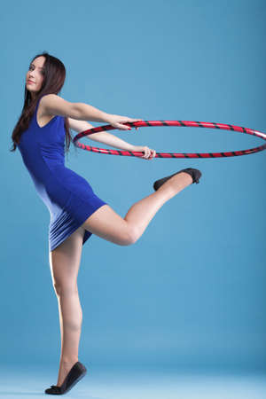 Beautiful woman in a sport wear. Dance hoop gym exercises blue background photo