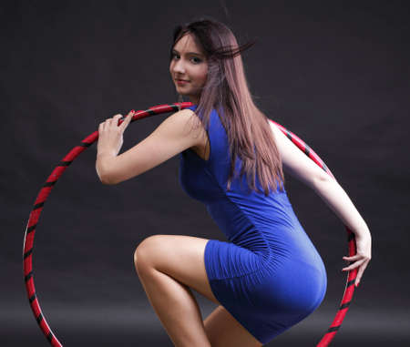 Beautiful woman in a sport wear. Dance hoop gym exercises black background Stock Photo - 12070998