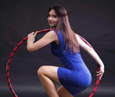 Hermosa mujer en un desgaste del deporte. Gimnasio, danza del aro ejerce fondo negro Foto de archivo - 12070998