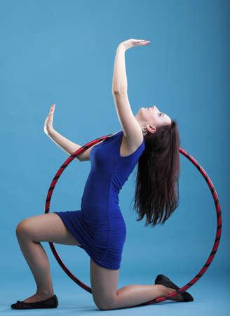 Hermosa mujer en un desgaste del deporte. Gimnasio, danza del aro ejerce fondo azul Foto de archivo - 12063254
