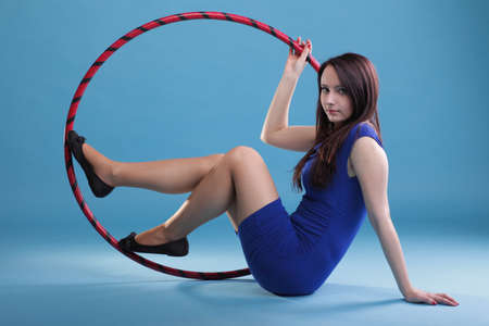 Hermosa mujer en un desgaste del deporte. Gimnasio, danza del aro ejerce fondo azul Foto de archivo - 12071042