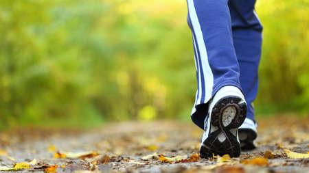 pieds sales: Une femme marche de cross-country et le sentier en forêt d'automne Banque d'images