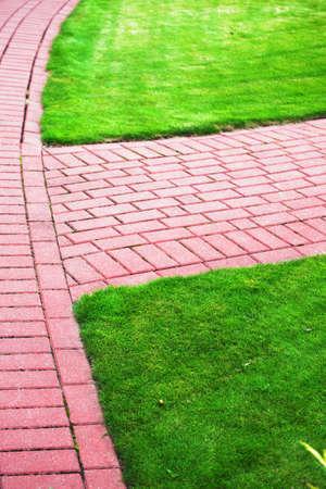 adoquines: Sendero del jard�n de piedra con la hierba creciendo entre y alrededor de las piedras, acera de ladrillo