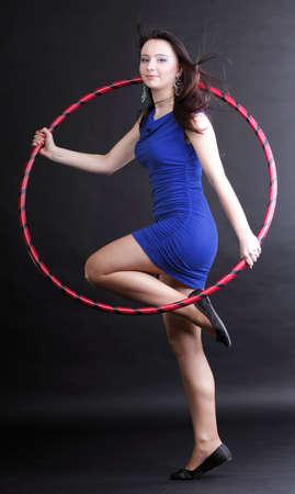 Beautiful woman in a sport wear. Dance hoop gym exercises black background photo