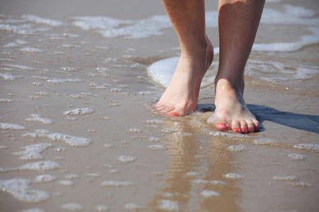 buenas piernas en el agua, bonita pedicura uñas rojo playa de arena