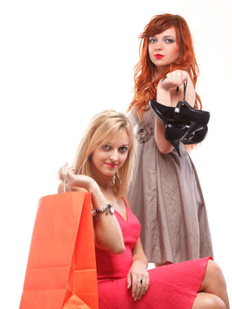 ginger haired: two happy girls,a ginger haired and a blonde haired holding shopping bags,shoes over white background