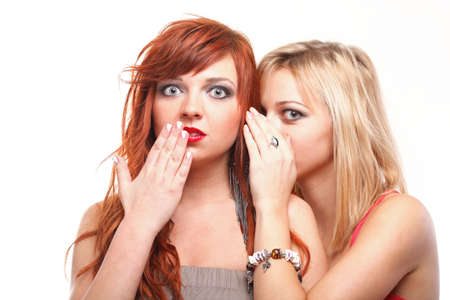 two happy girlfriends gossiping in white background - society gossip, rumor, rumour. photo