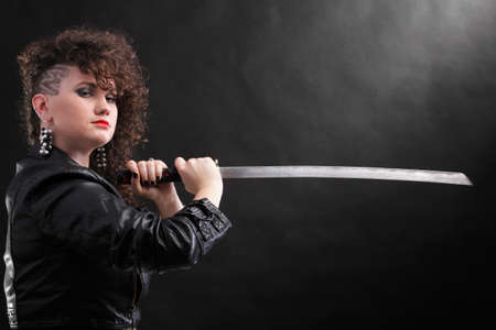 Woman with multiple ear piercings and dark natural brown-haired hands holding katana sword Stock Photo - 12662028