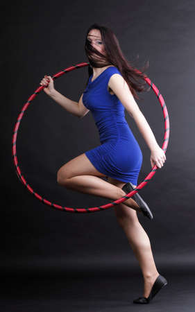 Beautiful woman in a sport wear with dance hoop, doing gym\ exercises in black background