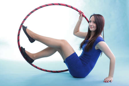 Beautiful woman in a sport wear with dance hoop, doing gym exercises in blue background photo