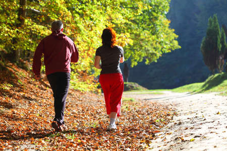 Woman and man walking cross country and trail in autumn forest Archivio Fotografico