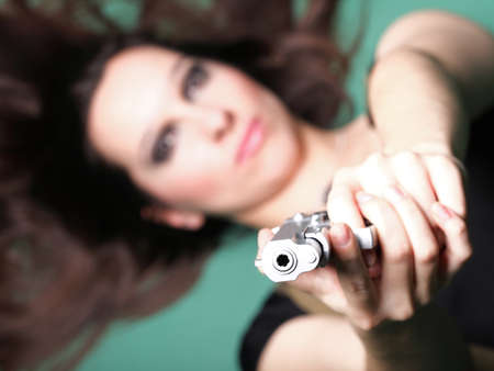 Sexy young woman in red with a gun, on green background photo
