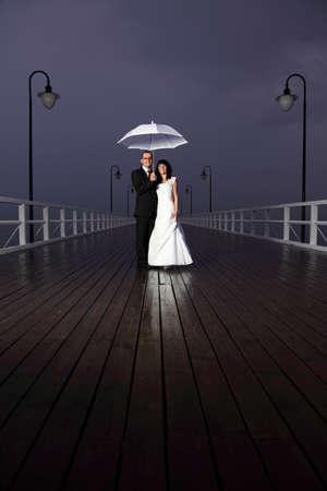 bride and groom, pier cloudy dusk sky. photo